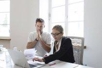 Молода жінка і чоловік, використовуючи ноутбук на столі — стокове фото