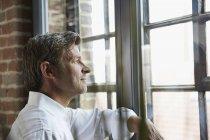 Бізнесмен дивиться з вікна — стокове фото