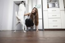 Young woman in kitchen playing with dog — Stock Photo