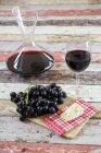 Blaue Trauben, Käse, Dekanter und Glas Rotwein — Stockfoto
