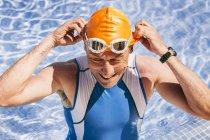 Улыбающийся пловец триатлета, стоящий в бассейне — стоковое фото