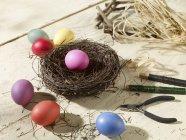 Nido di Pasqua con uova colorate, materiali artigianali su superficie di legno — Foto stock