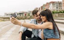 Espagne, Gijon, jeune couple amoureux prenant selfie avec smartphone — Photo de stock