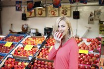 Smiling blond woman eating an apple in front of fruit stall on weekly market — Stock Photo