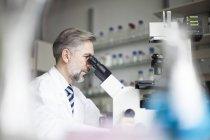 Científico en laboratorio viendo a través de microscopio - foto de stock