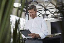 Здивований бізнесмен в офісі, дивлячись на цифровий планшетний — стокове фото