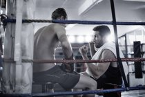 Boxer having a break with trainer in the corner of the boxing ring — Stock Photo