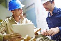 Bauarbeiter und Vorarbeiter diskutieren über Dachbalken — Stockfoto