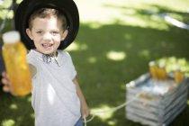 Garçon au jardin offrant une boisson fraîche — Photo de stock