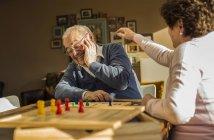 Couple de personnes âgées jouant ludo — Photo de stock