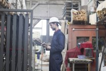 Warehouseman in storehouse holding clipboard — Stock Photo