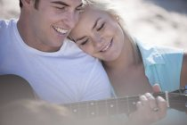 Young man playing guitar with girlfriend at beach — Stock Photo