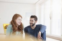 Young couple sitting on the floor of living room — Stock Photo