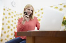 Smiling young woman with smartphone and laptop at her home office — Stock Photo