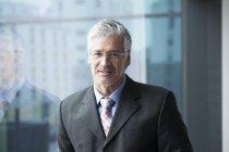 Empresário em pé à janela, retrato — Fotografia de Stock