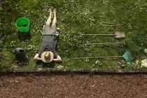 Vista aérea del hombre acostado en la hierba relajándose de la jardinería - foto de stock