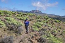 Spagna, Isole Canarie, La Gomera, Valle Gran Rey, escursionista femminile sul sentiero escursionistico La Merica, montagna Fortaleza sullo sfondo — Foto stock