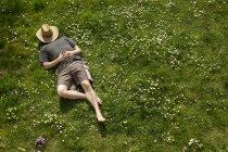 Чоловік лежить в траві розслабляючий вид зверху — стокове фото