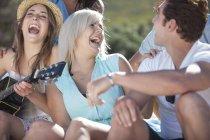 Amis avec la guitare s'amuser en plein air — Photo de stock