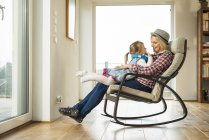 Mother and daughter on rocking chair with headphones — Stock Photo