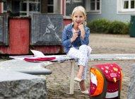Little girl doing homework at school yard — Stock Photo