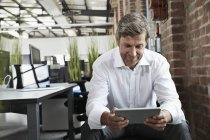 Бізнесмен в офісі, дивлячись на цифровий планшетний — стокове фото