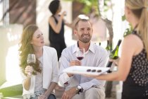 Waitress with tray and couple sitting outdoors tasting red wine — Stock Photo