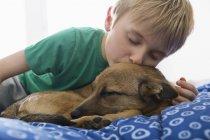 Niño y perro acurrucándose en la cama vista de cerca - foto de stock
