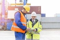 Deux hommes avec presse-papiers au port à conteneurs — Photo de stock