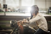 Boy pretending to drive vintage moped wearing helmet and googles — Stock Photo