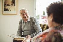 Senior man with photo album at home — Stock Photo