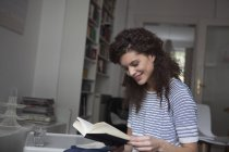 Young woman at home reading book — Stock Photo