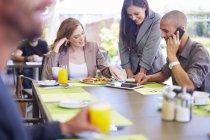 Ses collègues avec une tablette numérique à table à manger — Photo de stock