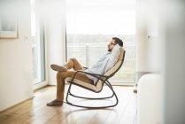 Молода людина, що сидить на крісло-гойдалка розслабляючий — стокове фото