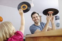 Father showing vinyl records to daughter — Stock Photo