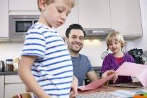 Padre armeggiare in cucina con figlio e figlia — Foto stock