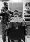 Hairdresser shaving young man's hair in a barbershop — Stock Photo