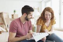 Jovem casal no apartamento novo, com caixas de papelão olhando para o chão plano — Fotografia de Stock