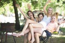 Verspielte Freunde im Urlaub auf dem gleichen Stuhl sitzen — Stockfoto