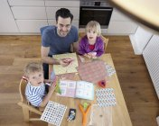 Father tinkering in kitchen with son and daughter — Stock Photo