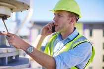Engineer on cell phone inspecting wind turbine — Stock Photo