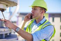 Инженер по сотовому телефону, проверка ветряной турбины — стоковое фото
