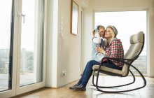 Mother and daughter on rocking chair sharing headphones — Stock Photo