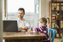 Father and daughter with laptop and game at wooden table — Stock Photo