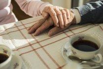 Старшие пары держатся за руки во время кофе-брейка — стоковое фото