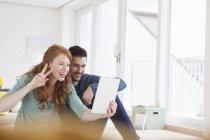 Jovem casal tomando uma selfie com tablet digital na sala de estar a sorrir — Fotografia de Stock