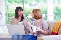 Due donne che si siedono sullo strato con il computer portatile e tazze — Foto stock