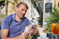 Spain, Mallorca, Arta, portrait of man sitting at courtyard of a cafe using smartphone — Stock Photo