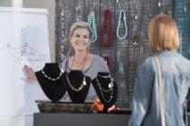 Женщина показывает клиенту дизайн ожерелья — стоковое фото