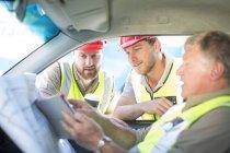 Строителей, обсуждает план строительства в автомобиле — стоковое фото